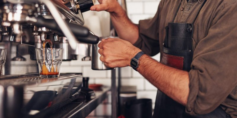 Cropped shot of barista using a coffee maker to prepare a cup of coffee. Cafe worker making a coffee.