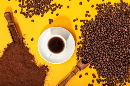 Coffee cup and roasted beans on yellow background. Coffee background. Top view