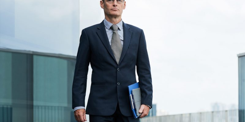 Confident serious company CEO with folder and tablet computer walking outdoors