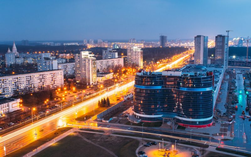 Minsk, Belarus. Aerial View Cityscape In Bright Blue Hour Evening And Yellow Illumination Spring Twilight. Construction Of Building Dana Mall In Independence Avenue